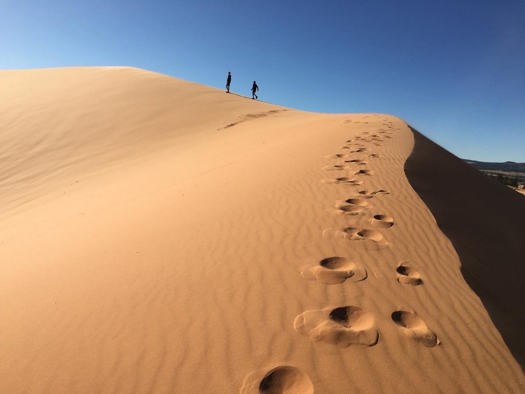 pink sand dune with footprints
