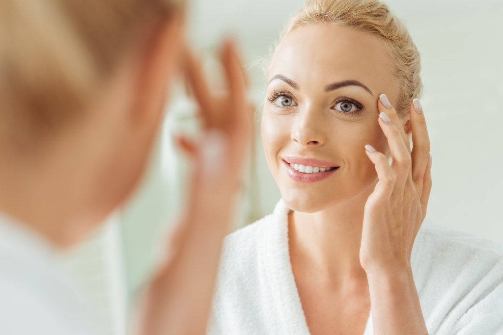 a woman looking in the mirror and using all natural anti aging cream