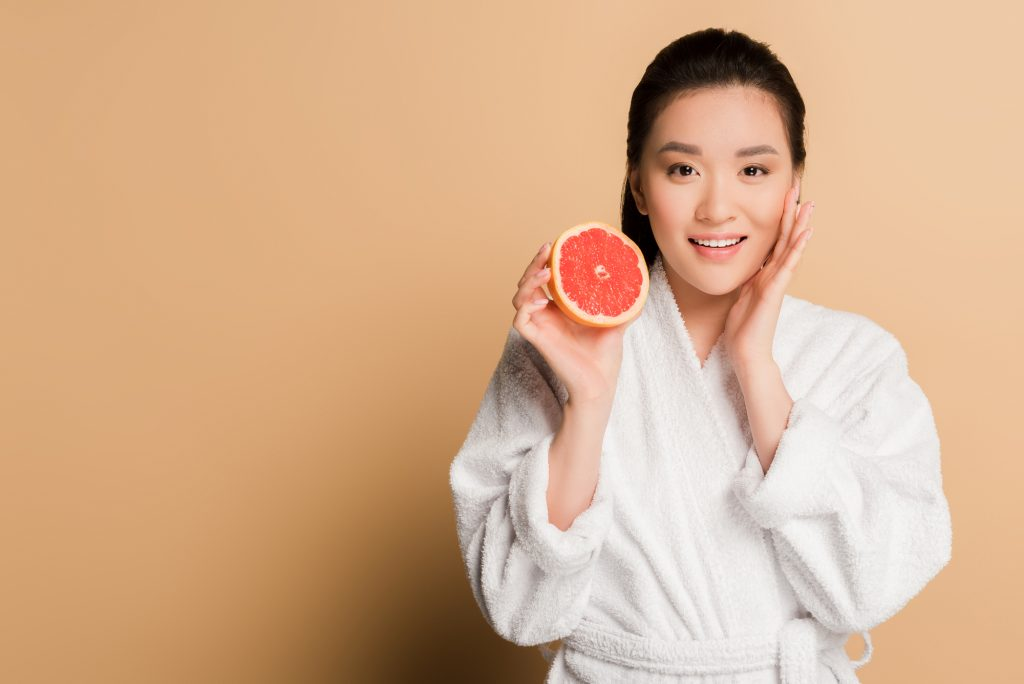 organic anti aging cream on a woman holding a grapefruit